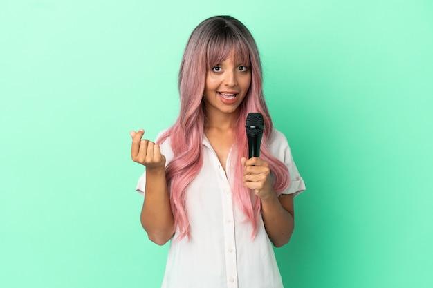 Молодая певица смешанной расы с розовыми волосами, изолированными на зеленом фоне, делает денежный жест