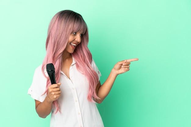 Молодая певица смешанной расы с розовыми волосами изолирована на зеленом фоне, указывая пальцем в сторону и представляет продукт