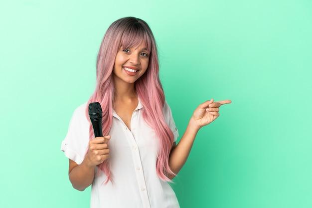 Молодая певица смешанной расы с розовыми волосами, изолированными на зеленом фоне, указывая пальцем в сторону