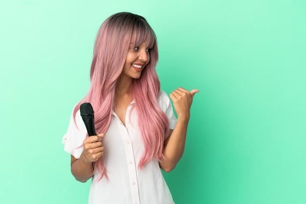 Молодая певица смешанной расы с розовыми волосами, изолированными на зеленом фоне, указывая в сторону, чтобы представить продукт