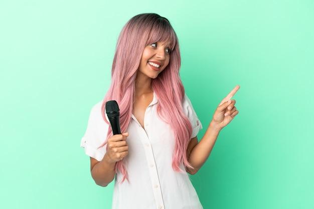 Молодая певица смешанной расы с розовыми волосами изолирована на зеленом фоне, указывая на отличную идею