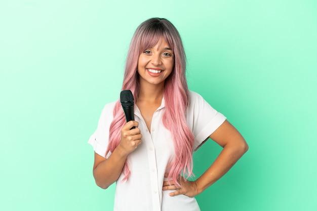 Молодая певица смешанной расы с розовыми волосами, изолированными на зеленом фоне, позирует с руками на бедрах и улыбается