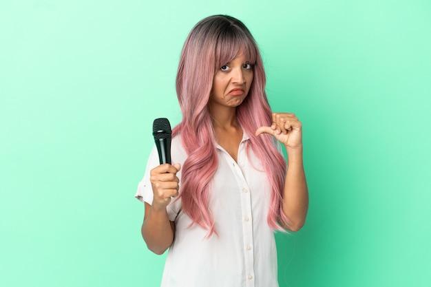 Молодая певица смешанной расы с розовыми волосами изолирована на зеленом фоне, гордая и самодовольная