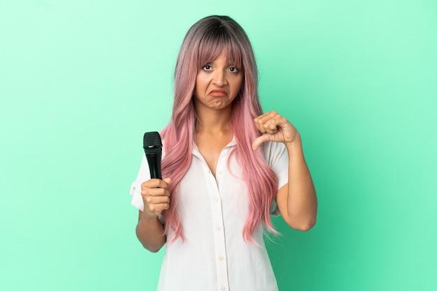 否定的な表現で親指を示す緑の背景に分離されたピンクの髪を持つ若い混血歌手の女性
