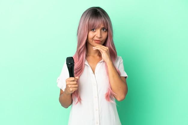 Молодая певица смешанной расы с розовыми волосами, изолированными на зеленом фоне, думает