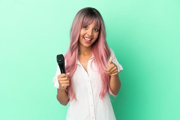 Молодая певица смешанной расы с розовыми волосами изолирована на зеленом фоне с большими пальцами руки вверх, потому что произошло что-то хорошее