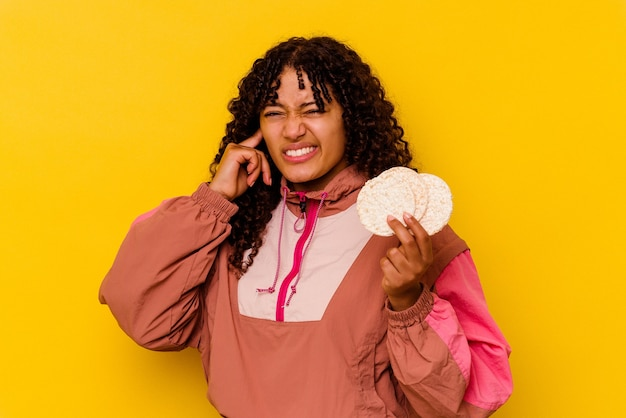 手で耳を覆う黄色の餅を持っている若い混血スポーツの女性。