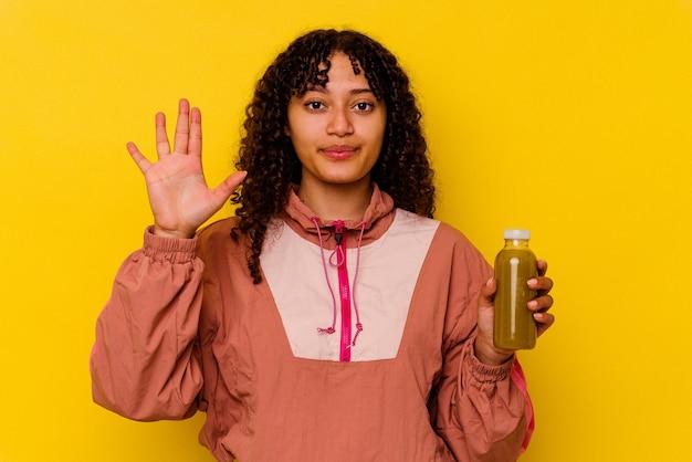 노란색 배경에 고립 된 스무디를 들고 젊은 혼혈 스포츠 여자
