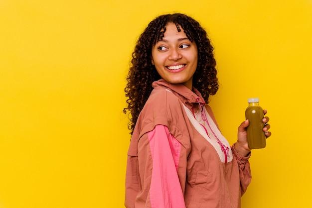 노란색 벽에 고립 된 스무디를 들고 젊은 혼혈 스포츠 여자