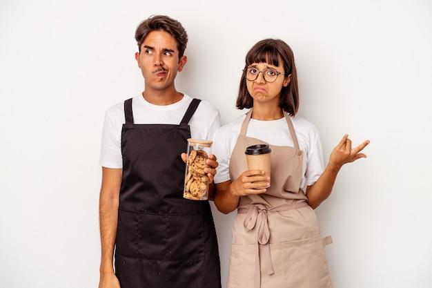 白い背景で隔離の若い混血店の店員のカップルは混乱し、疑わしく、不安を感じています。