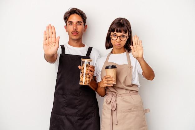 一時停止の標識を示す伸ばした手で立っている白い背景で隔離の若い混血店の店員のカップルは、あなたを防ぎます。