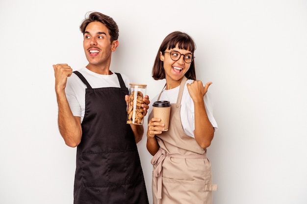 Young mixed race store clerk couple isolated on white background points with thumb finger away, laughing and carefree.