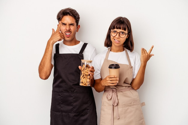 Young mixed race store clerk couple isolated on white background showing a disappointment gesture with forefinger.