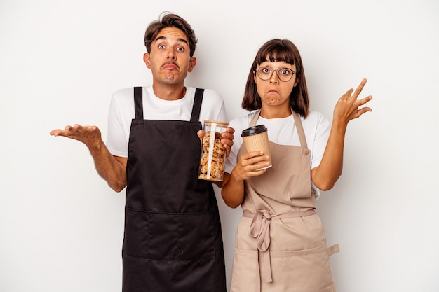 Young mixed race store clerk couple isolated on white background shrugs shoulders and open eyes confused.