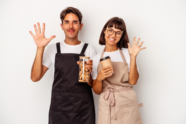 Young mixed race store clerk couple isolated on white background smiling cheerful showing number five with fingers.