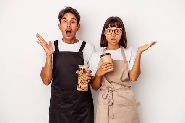 Young mixed race store clerk couple isolated on white background surprised and shocked.