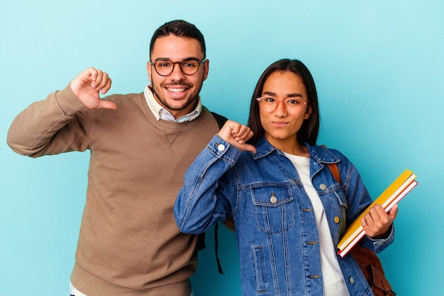 Young mixed race student couple isolated on blue feels proud and self confident, example to follow.