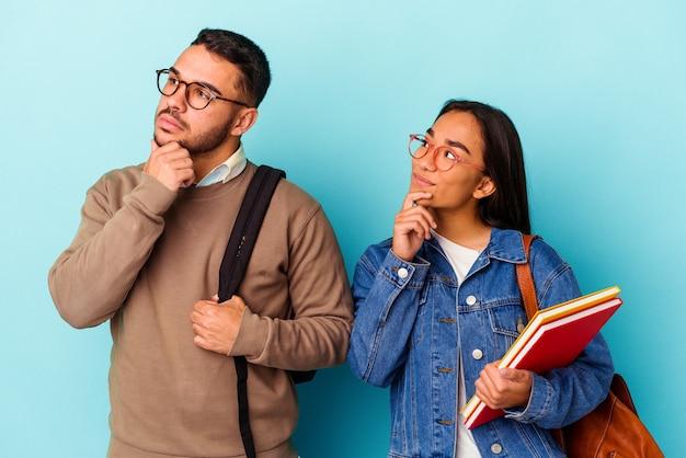 青い背景に分離された若い混血学生カップルが、疑わしい、懐疑的な表情で横を向いています。