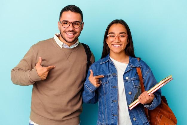誇りと自信を持って、シャツのコピースペースを手で指している青い背景の人に分離された若い混血学生カップル