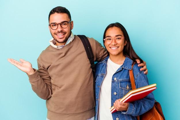 青の背景に若い混血学生のカップルが、手のひらにコピースペースを示し、腰に別の手を持っている。