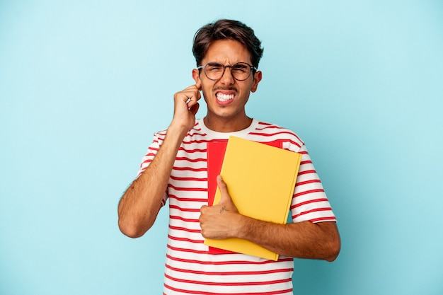 Young mixed race student man holding books isolated on blue background covering ears with hands.