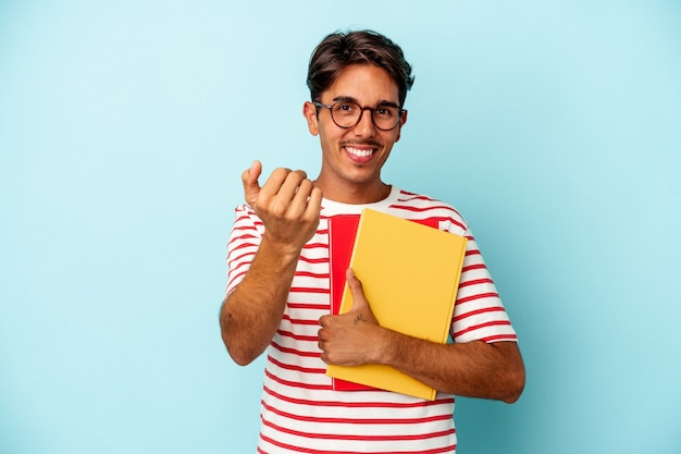 Young mixed race student man holding books isolated on blue background pointing with finger at you as if inviting come closer.
