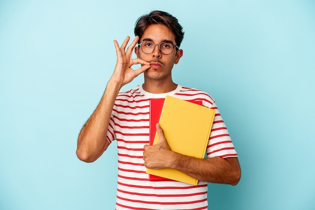 Young mixed race student man holding books isolated on blue background with fingers on lips keeping a secret.
