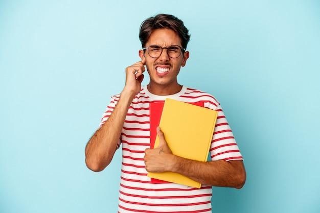 手で耳を覆う青い背景で隔離の本を保持している若い混血学生の男。