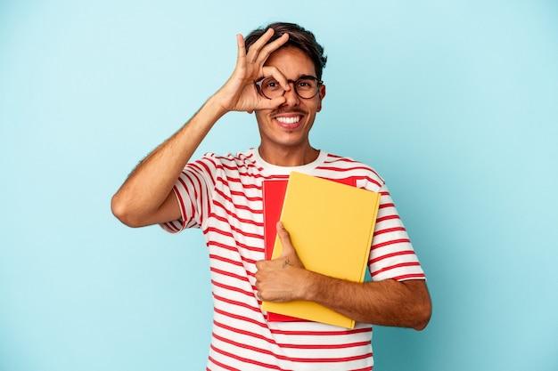 青い背景で隔離の本を保持している若い混血の学生の男は、目に大丈夫なジェスチャーを維持することに興奮しました。