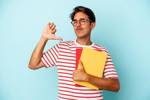 青い背景で隔離された本を持っている若い混血の学生の男は、誇りと自信を持って、従うべき例を感じます。