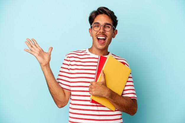 青い背景に分離された本を持っている若い混血の学生の男は、嬉しい驚きを受け取り、興奮し、手を上げます。