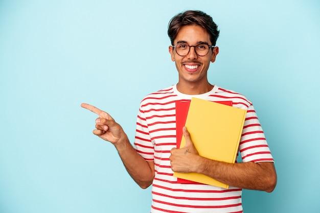 青い背景に分離された本を持っている若い混血の学生の男は、笑顔で脇を指して、空白のスペースで何かを示しています。