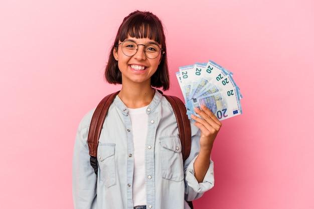 ピンクの背景に分離された手形を保持している若い混血学生女性幸せ、笑顔、陽気な。