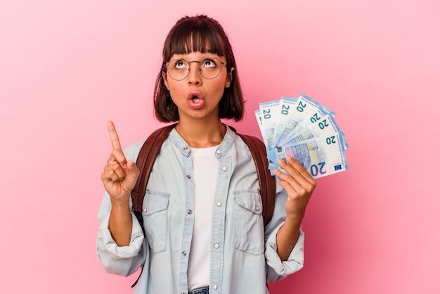 ピンクの背景に分離された手形を保持している若い混血学生女性は、口を開けて逆さまを指しています。