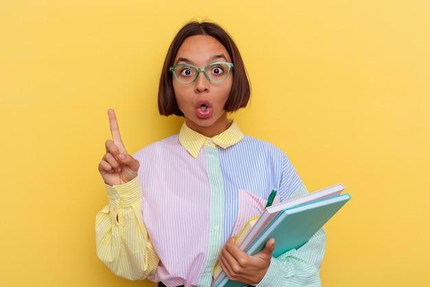 몇 가지 좋은 아이디어, 창의성의 개념을 갖는 노란색 배경에 고립 된 젊은 혼합 된 인종 학생 여자.