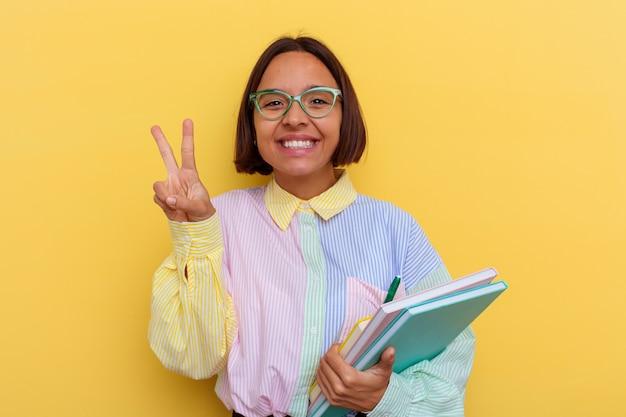 指で2番目を示す黄色の背景に分離された若い混血学生女性。