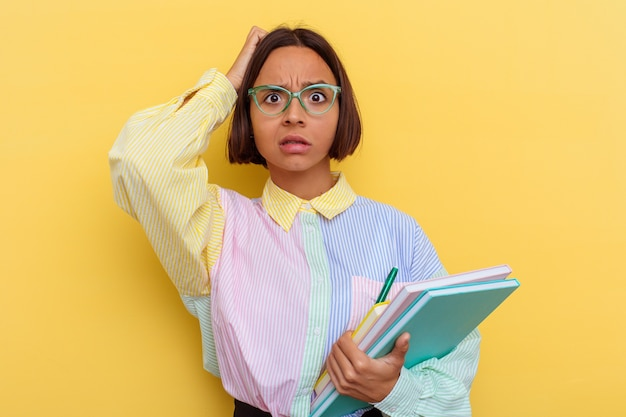 Young mixed race student woman isolated on yellow wall being shocked, she has remembered important meeting.
