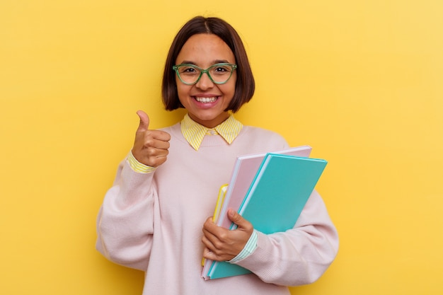 Young mixed race student woman isolated on yellow wall
