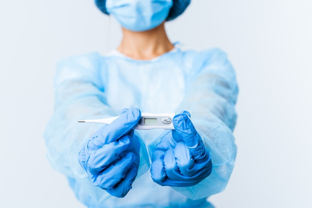 Young mixed race surgeon woman holding a thermometer isolated