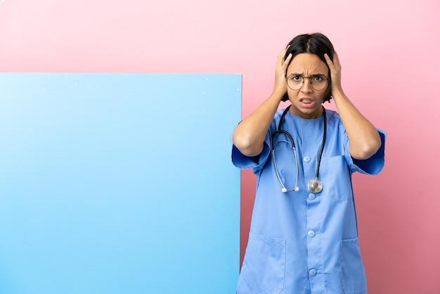 Молодая женщина-хирург смешанной расы с большим баннером на изолированном фоне делает нервный жест Premium Фотографии