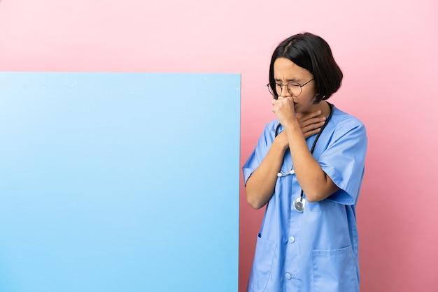 기침을 많이하는 격리 된 배경 위에 큰 배너와 함께 젊은 혼혈 외과 의사 여자