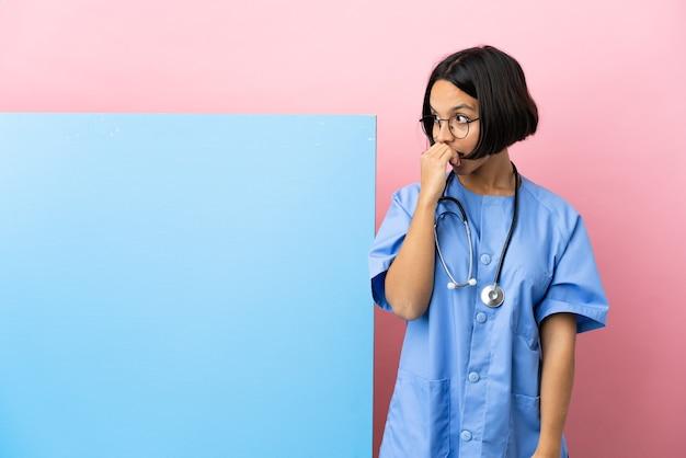 Молодая женщина-хирург смешанной расы с большим баннером на изолированном фоне делает неожиданный жест, глядя в сторону