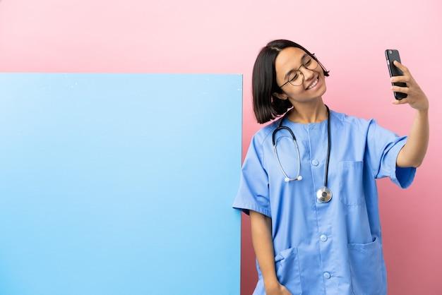 セルフィーを作る孤立した背景の上に大きなバナーを持つ若い混血外科医の女性
