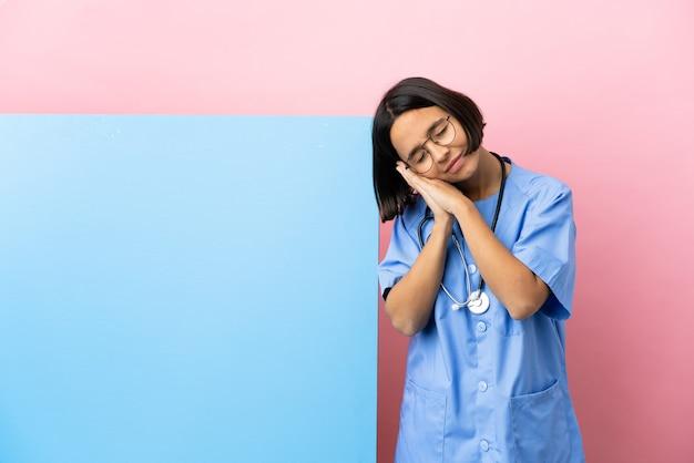 Dorable 식에서 수면 제스처를 만드는 격리 된 배경 위에 큰 배너와 젊은 혼합 된 인종 외과 의사 여자