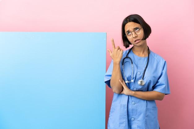 Молодая женщина-хирург смешанной расы с большим знаменем на изолированном фоне делает жест безумия, положив палец на голову