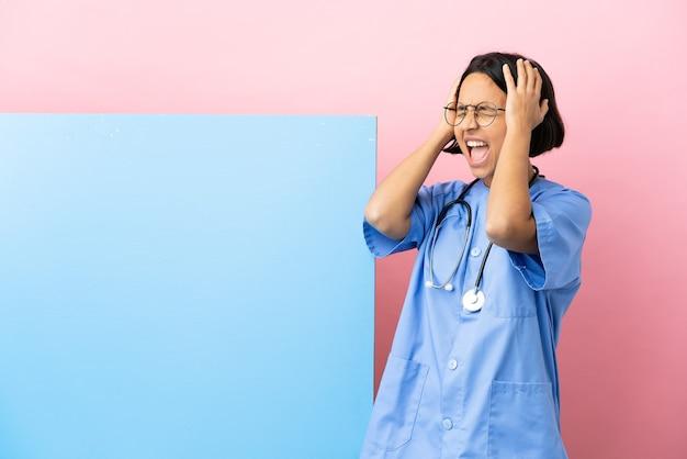 圧倒的に強調された孤立した背景の上に大きなバナーを持つ若い混血外科医の女性