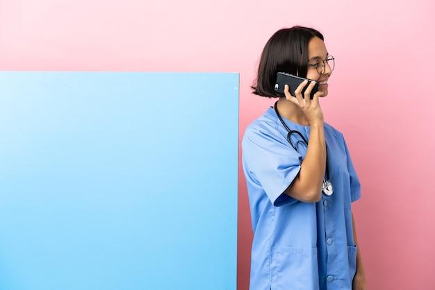 누군가와 휴대 전화로 대화를 유지하는 고립 된 벽 위에 큰 배너와 함께 젊은 혼혈 외과 의사 여자