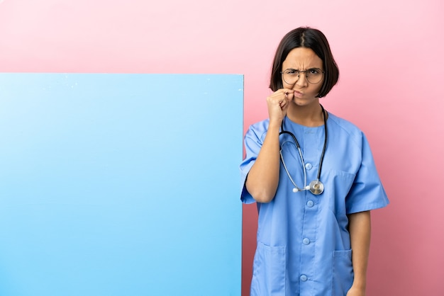 Young mixed race surgeon woman with a big banner over isolated background showing a sign of silence gesture