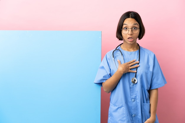 Young mixed race surgeon woman with a big banner over isolated background surprised and shocked while looking right