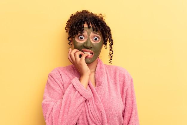 노란색 배경에 격리된 안면 마스크를 쓴 젊은 혼혈 인종은 손톱을 물어뜯고 긴장하고 매우 불안합니다.
